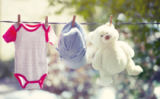 Erika Eros - Baby clothes, hat and teddy hanging on the clothesline